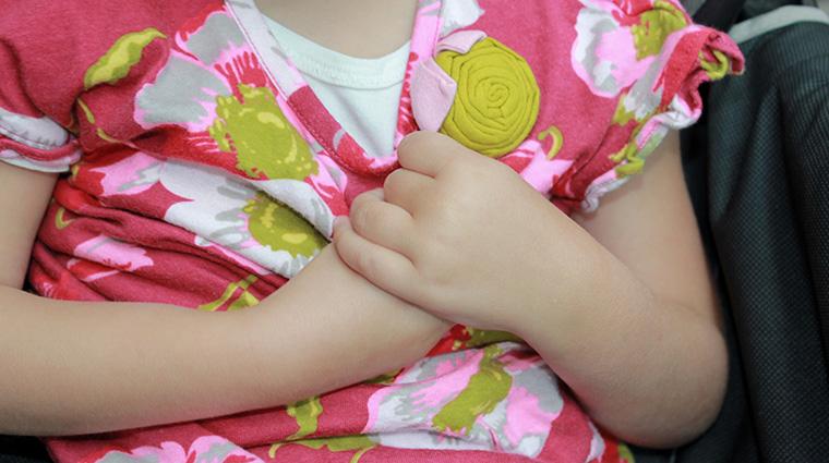 Little girl holding her own hands