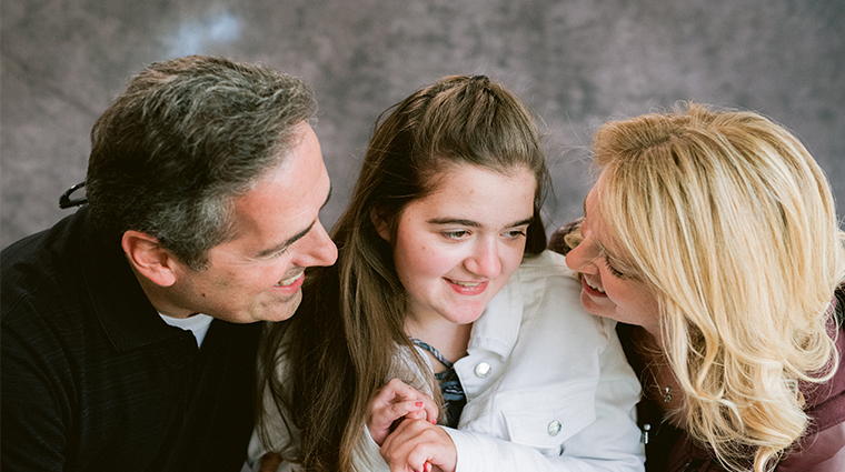 Young girl smiling with her parents