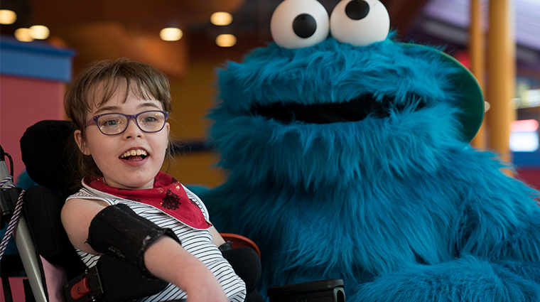Young girl smiling with Cookie Monster